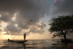 Silueta de los pescadores que lanzan los pescados netos el tiempo de la puesta del sol Foto de archivo