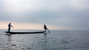 Silueta de los pescadores que se baten por las piernas en el lago Inle, Myanmar imagenes de archivo