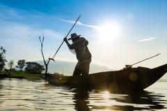 Silueta de los pescadores que usan gallinero-como pescados de cogida de la trampa en la foto de archivo libre de regalías