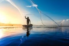 Silueta de los pescadores que usan gallinero-como pescados de cogida de la trampa en la imagenes de archivo