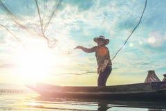 Silueta de los pescadores que usan gallinero-como pescados de cogida de la trampa en el lago con el paisaje hermoso de la salida  fotografía de archivo libre de regalías