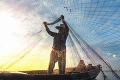 Silueta de los pescadores que usan gallinero-como pescados de cogida de la trampa en el lago con el paisaje hermoso de la salida  imagen de archivo libre de regalías