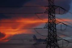 Silueta de los posts de la electricidad antes del cielo azul tan hermoso de la puesta del sol Imagen de archivo