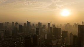 Silueta de los rascacielos de Jakarta en el tiempo de la puesta del sol Foto de archivo