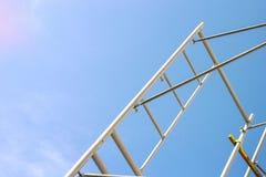 Silueta de los trabajadores de construcción en el funcionamiento del andamio debajo de un cielo azul imagen de archivo