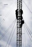 Silueta de los trabajadores que reparan la torre de comunicación Imágenes de archivo libres de regalías
