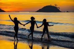 Silueta de muchachas en la puesta del sol Fotos de archivo libres de regalías