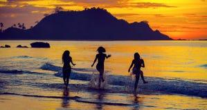 Silueta de muchachas en la puesta del sol Foto de archivo libre de regalías