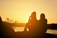 Silueta de mujeres felices en la roca cerca del río Imágenes de archivo libres de regalías