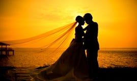 Silueta de pares en amor en la puesta del sol fotos de archivo