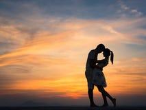 Silueta de pares en la puesta del sol Fotos de archivo libres de regalías