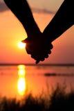 Silueta de pares en la puesta del sol que lleva a cabo las manos foto de archivo libre de regalías