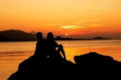Silueta de pares jovenes en amor en el beac Foto de archivo libre de regalías