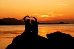 Silueta de pares jovenes en amor en la playa Fotografía de archivo