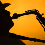 Silueta de Performae I del saxofón en el oro Imagen de archivo