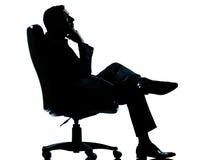 Silueta de relajación de la butaca del hombre de negocios que se sienta Imagen de archivo libre de regalías