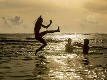 Silueta de saltar de la mujer joven del océano Imagen de archivo libre de regalías