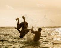 Silueta de saltar del hombre joven del océano Imagen de archivo libre de regalías