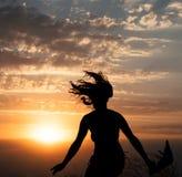 Silueta de salto de la chica joven con el mantón en fondo del cielo nublado hermoso con puesta del sol anaranjada Fotos de archivo libres de regalías
