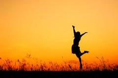 Silueta de salto de la mujer y de la puesta del sol imagenes de archivo