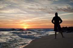 Silueta de salto del hombre en la playa en la puesta del sol Fotos de archivo libres de regalías