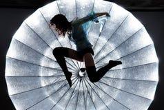 Silueta de salto del ` s de la mujer sobre fondo brillante Fotos de archivo libres de regalías