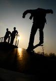 Silueta de skateres en parque Imagen de archivo libre de regalías