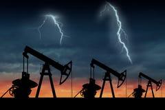 Silueta de tres bombas de aceite en la puesta del sol Imagen de archivo