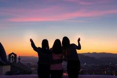 Silueta de tres muchachas que miran a la puesta del sol fotos de archivo libres de regalías