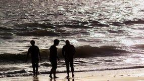 Silueta de tres muchachos que juegan en la playa Fotografía de archivo