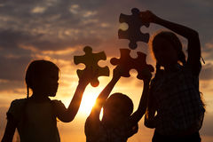 Silueta de tres niños felices en quienes que juegan en el campo Imágenes de archivo libres de regalías
