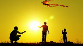 Silueta de tres personas irreconocibles Los niños y el padre felices están jugando con una cometa en la puesta del sol Educación  almacen de video