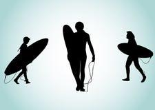 Silueta de tres personas que practica surf Fotos de archivo libres de regalías
