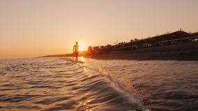 Silueta de un adolescente que corre alrededor de la línea de la resaca en la puesta del sol almacen de video