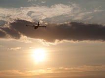 Silueta de un aeroplano en la puesta del sol Foto de archivo