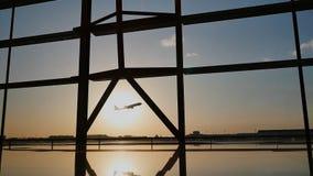 Silueta de un aeroplano que saca en la puesta del sol en el aeropuerto de Pekín en el fondo de una ventana almacen de metraje de vídeo