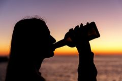 Silueta de un alcohol de consumición de la muchacha de una botella en la puesta del sol Foto de archivo libre de regalías