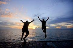 Silueta de un amigo que salta en el mar durante puesta del sol de oro imagen de archivo libre de regalías