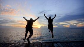 Silueta de un amigo que salta en el mar durante puesta del sol de oro foto de archivo libre de regalías