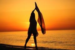 Silueta de un baile de la señora por el mar Imagen de archivo
