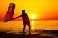 Silueta de un baile de la señora por el mar Fotografía de archivo