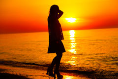 Silueta de un baile de la señora por el mar Imagen de archivo libre de regalías