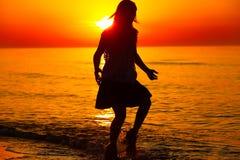 Silueta de un baile de la señora por el mar Imagenes de archivo