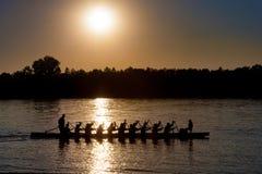 Silueta de un barco del dragón con el batimiento de gente en la puesta del sol en DA Fotografía de archivo libre de regalías