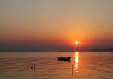 Silueta de un barco durante salida del sol Foto de archivo libre de regalías