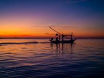 Silueta de un barco de pesca en los rayos del sol poniente con las nubes imagen de archivo