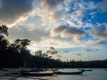 Silueta de un barco y de palmeras contra el sol poniente con las nubes imagenes de archivo