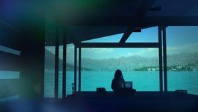 Silueta de un blogger que se sienta en un lugar del paraíso y que trabaja en el ordenador foto de archivo