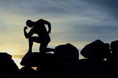 Silueta de un Bodybuilder en las rocas Imagenes de archivo