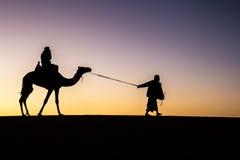 Silueta de un camello y un cameleer en la salida del sol Fotos de archivo